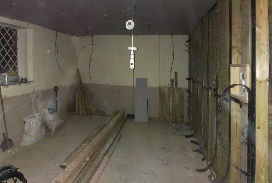 Insulation goes behind the first false wall. East and North walls still to be done - Dec 2012